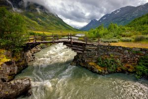 rushing river under wooden bridge with mountain range in background