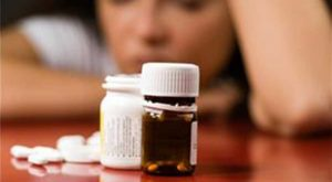 Woman looking at pill bottle dealing with depression
